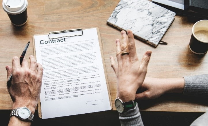Contract paper on desk between two people