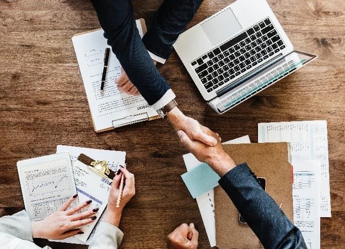 Business people shaking hands over desk