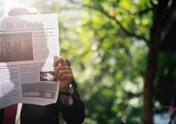 Man reads newspaper at park