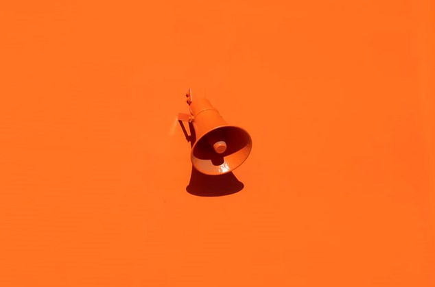 Megaphone installed on orange wall