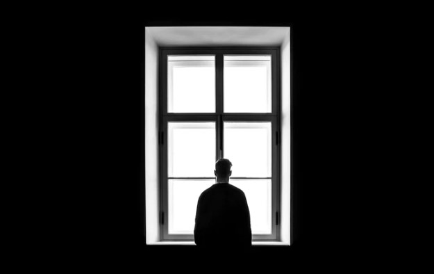 Man standing in a black room by window