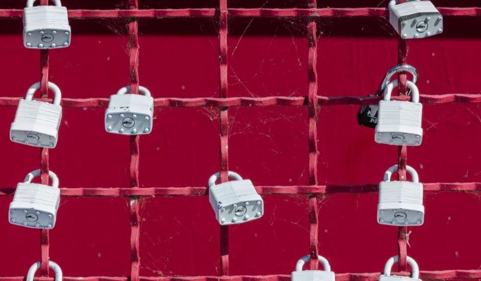 White locks hanging on red wall